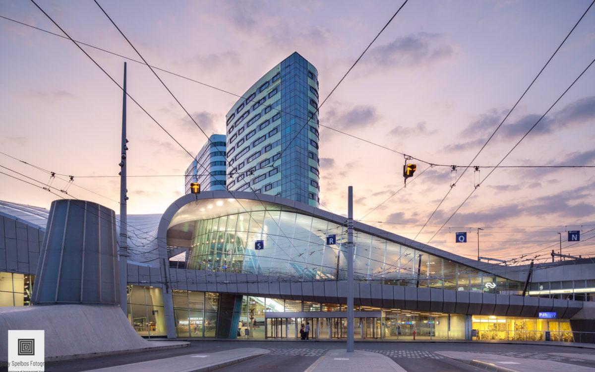 Het vooraanzicht van treinstation Arnhem Centraal na zonsondergang